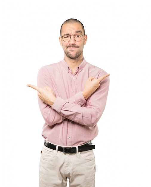 Confused young man poiting in both directions Premium Photo