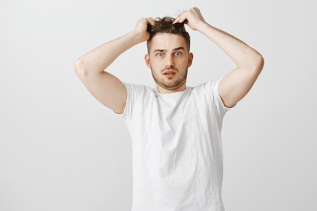 Смущенный молодой человек трогает волосы, нужна новая стрижка Бесплатные Фотографии