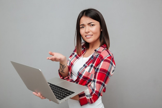 Confused young woman using laptop computer. Free Photo