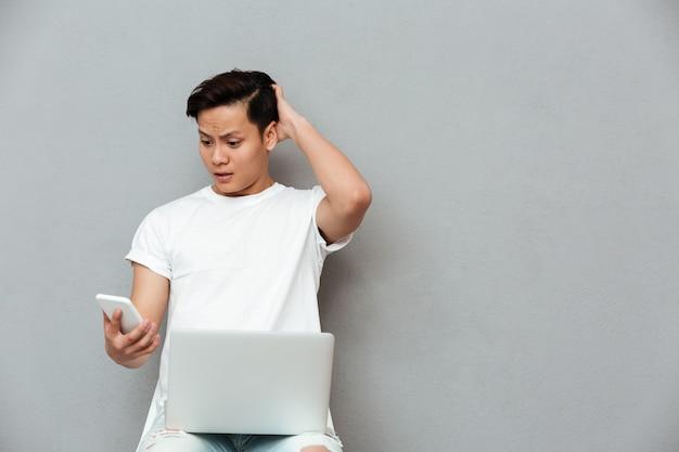 Confused молодой азиатский человек смотря мобильный телефон. Бесплатные Фотографии