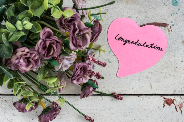 Congratulation note in heart shape paper with purple bouque Free Photo