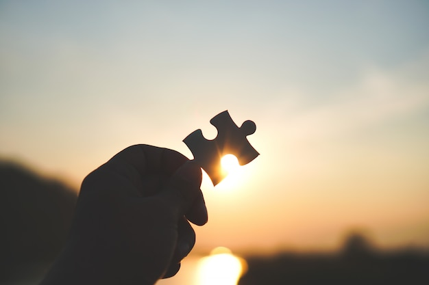 Connect jigsaw puzzle piece with sunset background. Premium Photo