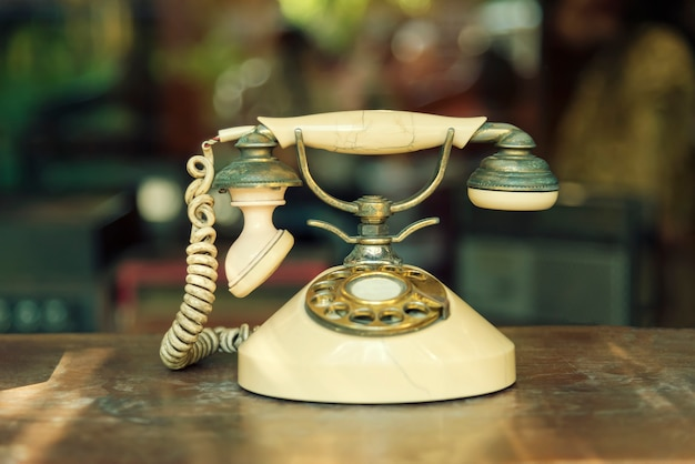 Connection technology concept. old telephone on wood table with blurred background. Premium Photo