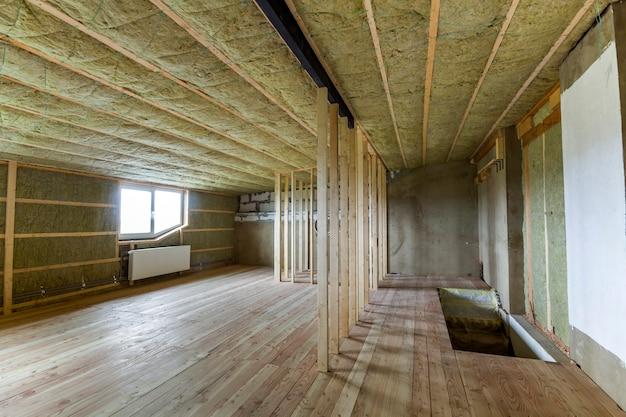 Строительство и ремонт большого светлого просторного пустого помещения с дубовым полом, стены и потолок утеплены каменной ватой, радиаторами отопления под низкими мансардными окнами и деревянным каркасом будущих стен. Premium Фотографии