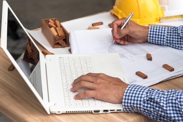 Construction concept, hands of engineer working on blueprint Premium Photo