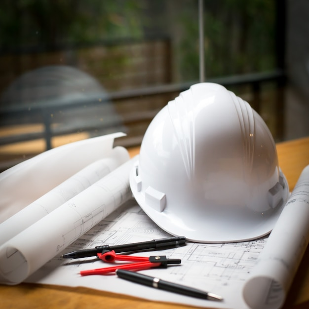 construction concept image helmet rolled blueprints on wooden boards in retro style. Free Photo