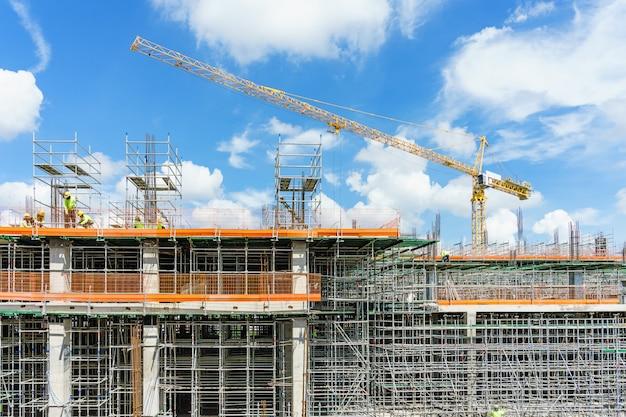 Construction cranes and high-rise building under construction against blue sky. Premium Photo