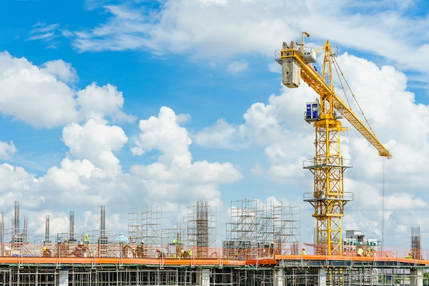Construction cranes and high-rise building under construction against blue sky. Premium Photo