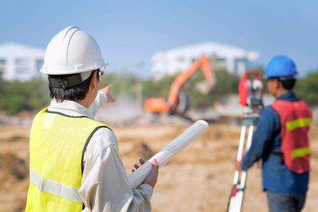 Construction engineer hodling construction drawing with foreman at site Premium Photo