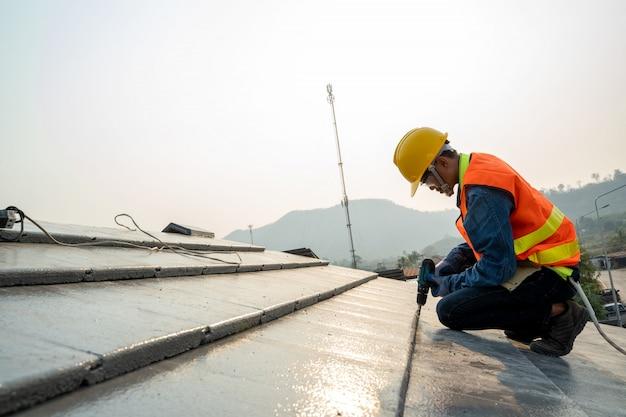 Строительный инженер надевает форму безопасности инспектора кровельщика, работающего на конструкции крыши здания на строительной площадке. Premium Фотографии