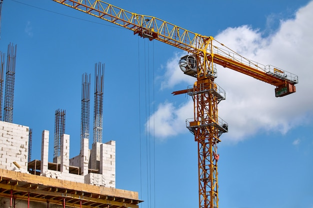 Construction of a high-rise building, the formation of cement supports and the operation of a crane against a blue sky, selective focus Premium Photo