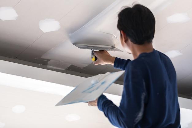Construction man worker plaster gypsum ceiling for interior build gypsum board ceiling Premium Photo