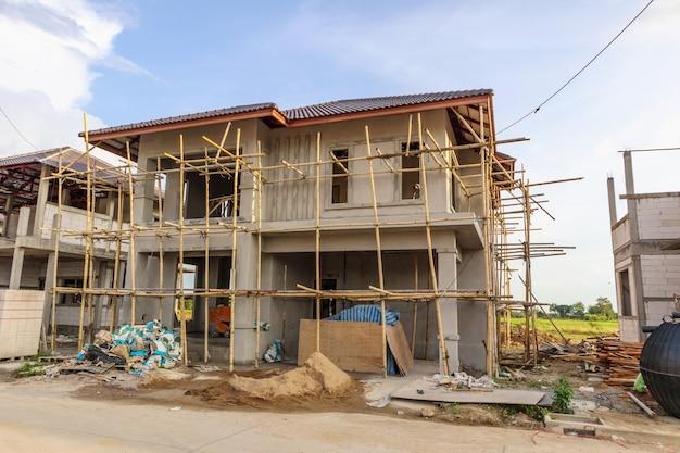 雲と青い空とサイトの構築で進行中の建設住宅の新しい家 Premium写真