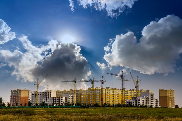 Construction site of a new apartment high building with tower cranes against blue sky. Premium Photo