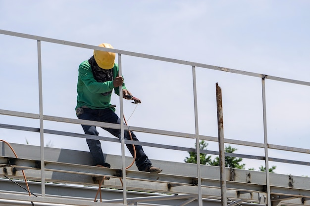 In the construction site, the welding workers at work at top roof. Premium Photo