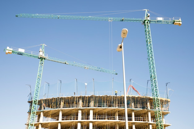 Construction site with crane and building against blue sky Free Photo