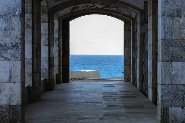 Construction with arch rocky coast & translucent sea Premium Photo