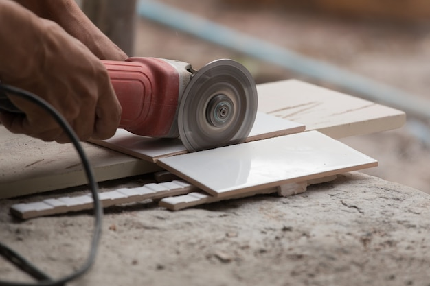 Construction Worker Cutting A Tile Using An Angle Grinder Photo