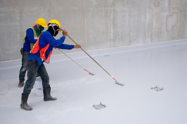 Construction worker epoxy painting at floor for water proof protection Premium Photo