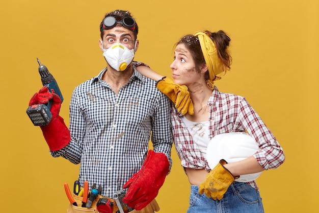 シャツと赤い手袋を身に着けている防護マスクの建設労働者は、大きな同情で彼を見ている彼の同僚の近くに立っています。人、建設、建物のコンセプト 無料写真