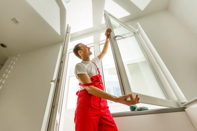 Construction worker installing window in house Premium Photo