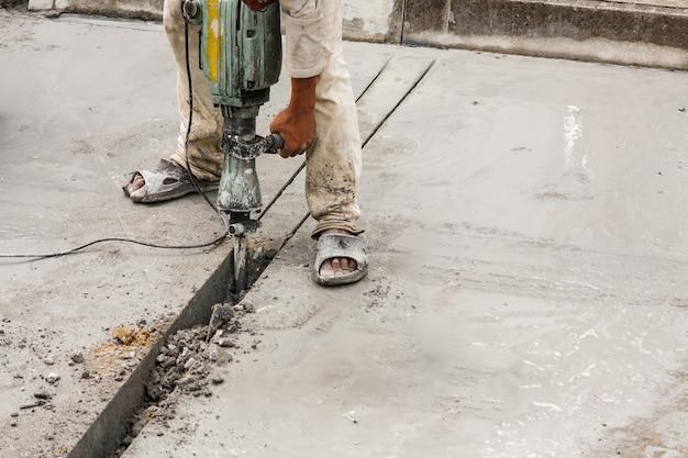 Строитель, используя отбойный молоток, сверля бетонную поверхность Premium Фотографии