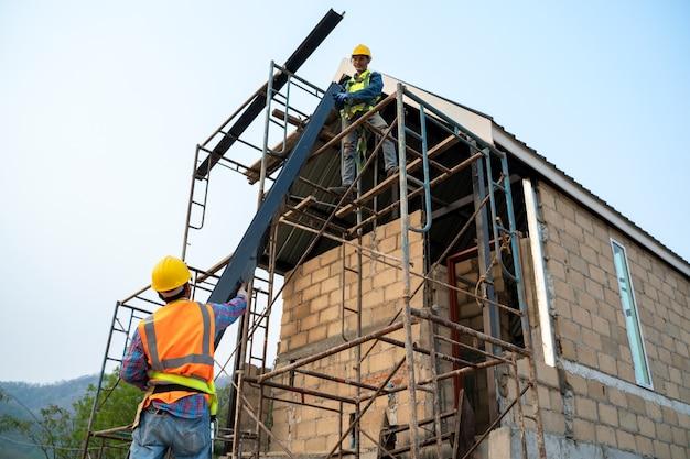 建設中の新しい家で足場に取り組んでいる安全ハーネスと安全ラインを身に着けている建設労働者。 Premium写真