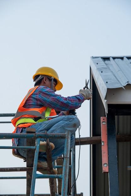 建設中の家で足場の作業中に安全ハーネスベルトを着用している建設作業員。 Premium写真
