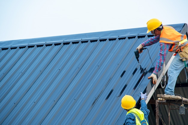Construction worker wearing safety harness using secondary safety device connecting into 15 mm static rope using as fall restraint shingle on top of the new roof. Premium Photo