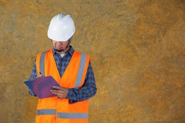 Рабочий-строитель с документом, планом работая для внутренней строительной площадки здания. Бесплатные Фотографии