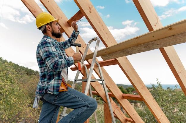 하드 모자와 망치로 집 지붕을 짓는 건설 노동자 프리미엄 사진
