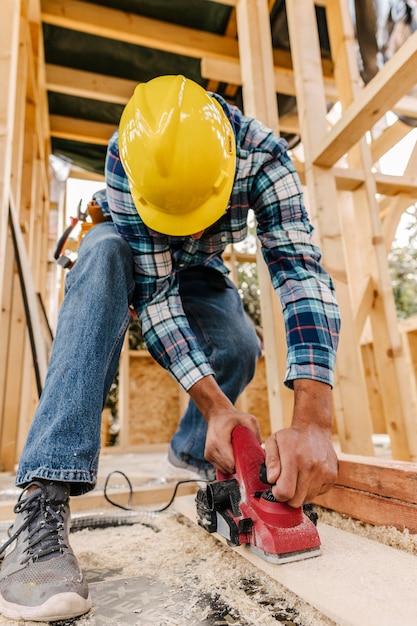 木片を紙やすりで磨くヘルメットをかぶった建設労働者 無料写真