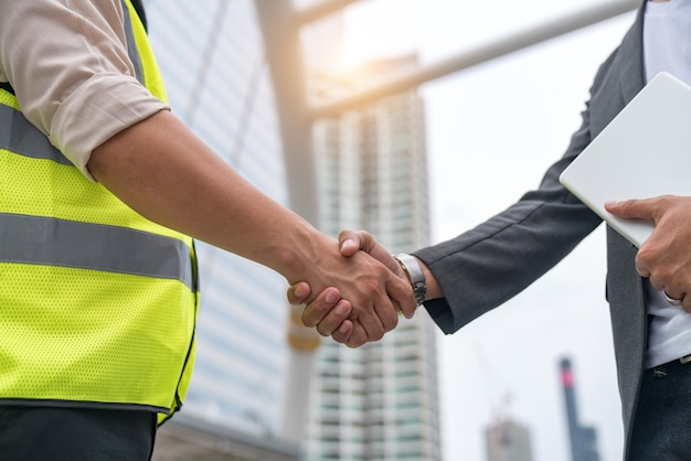 Premium Photo | Construction workers in protective helmets and vests are shaking  hands while working