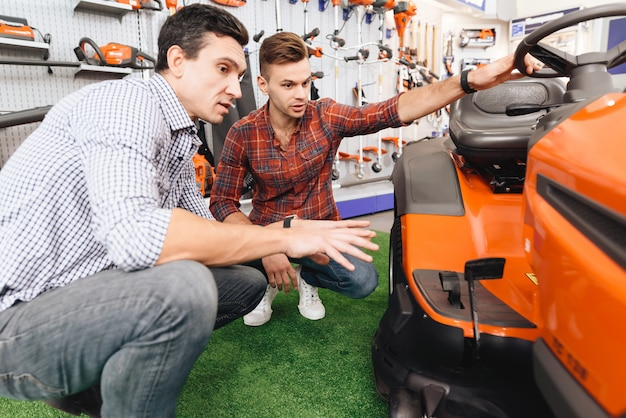 Consultant in garden tools store shows customer lawn mower. Premium Photo