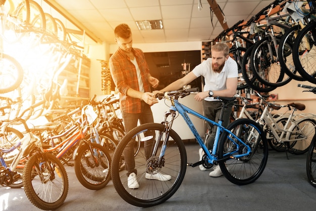 Consultant shows bicycle to client in sport shop Premium Photo