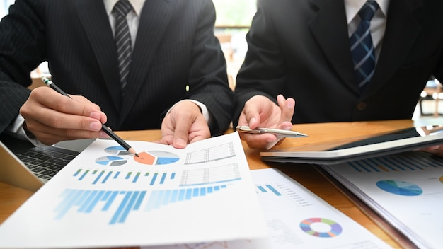 Consulting business with two man analysis finance data with device and paper document. Premium Photo