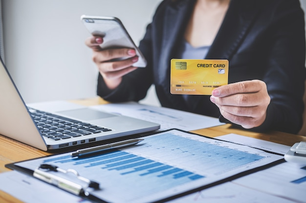 Consumer holding smartphone, credit card and typing on laptop for online shopping and payment Premium Photo