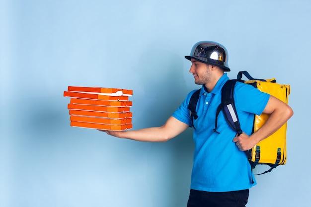 検疫中の非接触配送サービス。男は断熱中に食べ物や買い物袋を届けます。青に分離された配達員の感情 無料写真