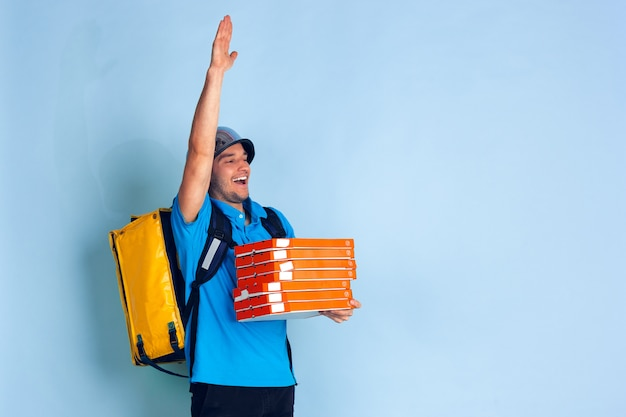 Бесконтактная служба доставки во время карантина. человек доставляет еду и сумки во время изоляции. эмоции доставщика, изолированных на синем Бесплатные Фотографии