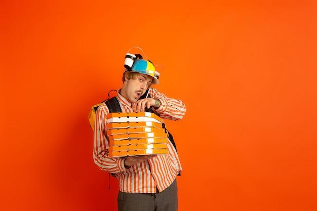 Бесконтактная служба доставки во время карантина. человек доставляет еду и сумки во время изоляции. эмоции доставщика, изолированные на оранжевый Бесплатные Фотографии