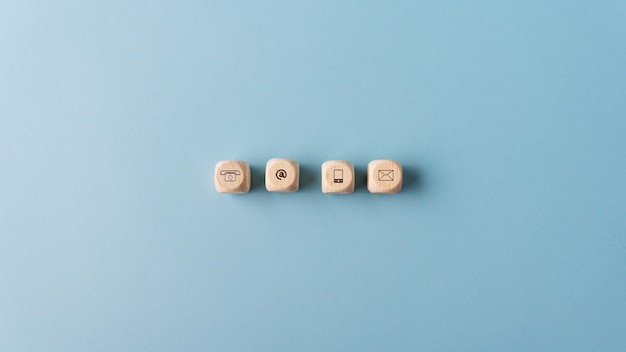 Contact and communication icons on wooden dices Premium Photo