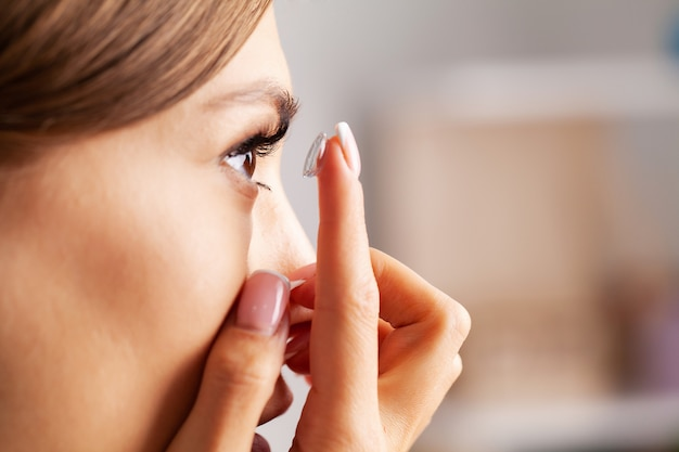 Contact lens for vision. young woman puts on optical lenses at home in the room Premium Photo