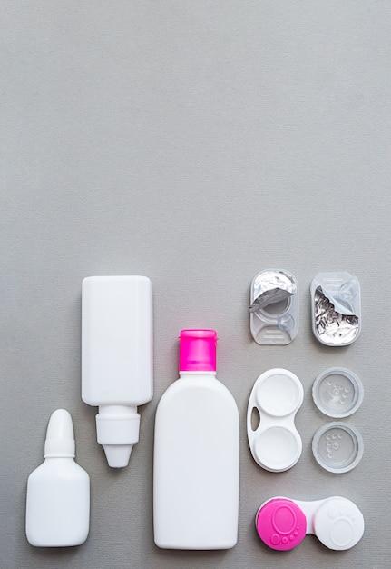 Контактные линзы и аксессуары плоско лежат на сером фоне Premium Фотографии