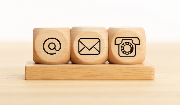 Contact us concept. wooden blocks with email, mail and telephone icons.website page contact us or e-mail marketing Premium Photo