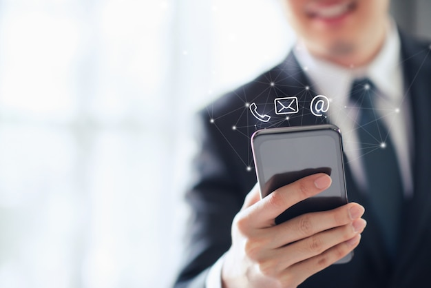 Contact us, happy businessman holding mobile smartphone with mail, phone and email icons Premium Photo