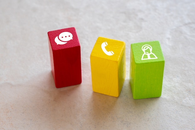 Contact us icon on colorful puzzle with hand Premium Photo