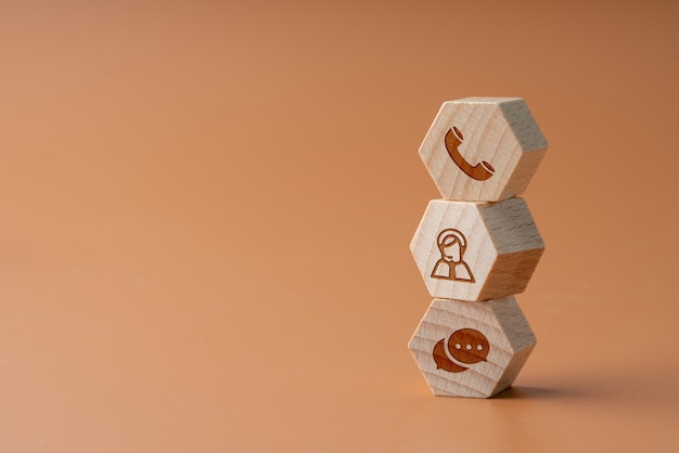 Contact us icon on wood puzzle with hand Premium Photo