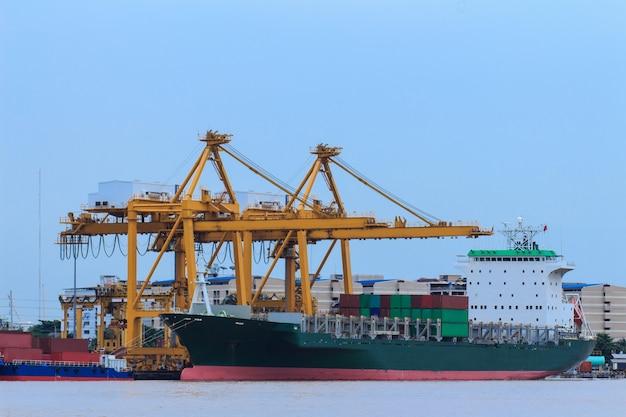 Грузовое судно контейнеровоз с работающим мостом крана на верфи в сумерках f Premium Фотографии