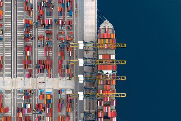 Погрузка контейнеровозов в порту, грузовые перевозки, импорт, экспорт и бизнес-логистика контейнеровозом, вид с воздуха. Premium Фотографии