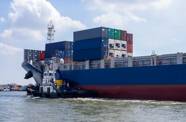 Container cargo ship with tugboat Premium Photo